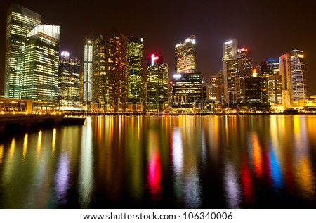 Singapore business district in the night time with water reflections