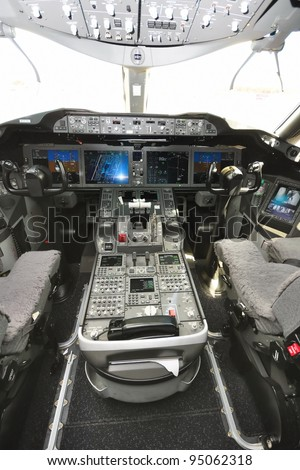 SINGAPORE - FEBRUARY 12: Interior of the cockpit with control panel and throttle in the new Boeing 787 Dreamliner at Singapore Airshow February 12, 2012 in Singapore - stock photo