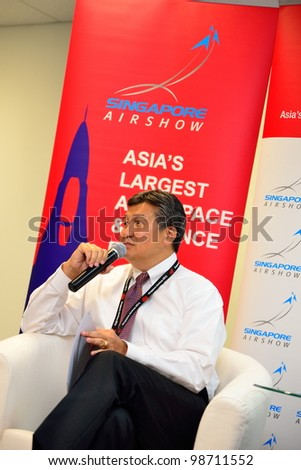 SINGAPORE - FEBRUARY 17: Mr Jimmy Lau, Managing Director of Experia Events, speaking at the wrap-up media briefing at Singapore Airshow February 17, 2012 in Singapore - stock photo