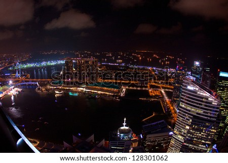 SINGAPORE, FEBRUARY 12 - Wide angle night time aerial view of Singapore city skyline including the Singapore Flyer and the Marina Bay Sands hotel along the Singapore river on Feb 12, 2013 Singapore. - stock photo