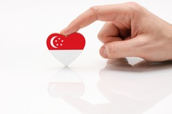 Singapore flag. Love and respect Singapore. A man's hand holds a heart in the shape of the Singapore flag on a white glass surface. The concept of patriotism and pride.