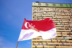 Singapore flag waving in the wind against background of peoples park old building; on bright beautiful sunny day with blue sky. Selective focus