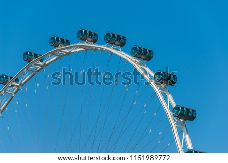 Singapore Flyer the Largest Ferris Wheel with cabins on blue sky in the World. #1151989772