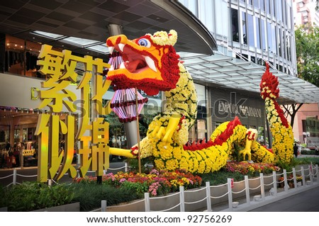 "SINGAPORE - JANUARY 13: Chinese New Year Floral Dragon sculpture in front of Mandarin Orchard Hotel on January 13, 2012 in Singapore. Theme of this year is ""Style up in spring at Mandarin Gallery"". - stock photo"