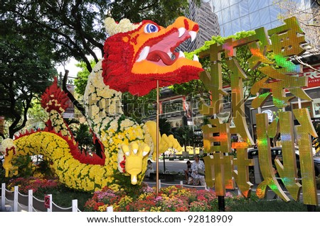 """SINGAPORE - JANUARY 13: Chinese New Year Floral Dragon sculpture in front of Mandarin Orchard Hotel on January 13, 2012 in Singapore. Theme of this year is """"Style up in spring at Mandarin Gallery""""."""