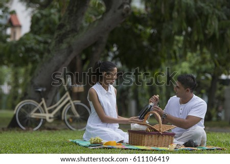 Singapore, Man and woman opening picnic basket with bicycle in background