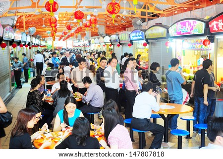 SINGAPORE - MARCH 6: Locals eat at a popular food hall on March 06, 2013 in  Singapore. Inexpensive food stalls are numerous in the city so most Singaporeans dine out at least once a day.