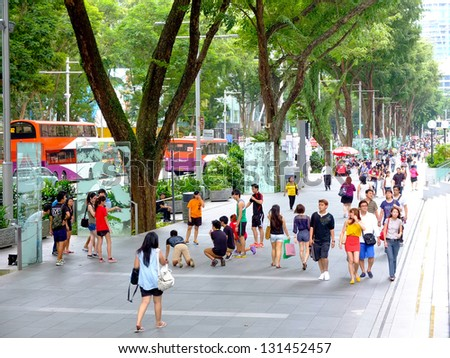 SINGAPORE - MARCH 8: Pedestrians walk along famous Orchard road on March 8, 2013 in Singapore. This 2.2 kilometre street is the retail and entertainment hub of Singapore and major tourist attraction.