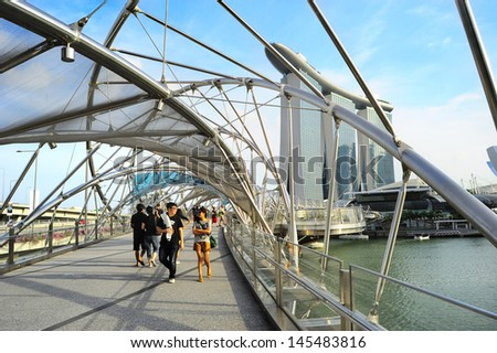 SINGAPORE - MAY 03: The Helix Bridge and Marina Bay Sands on May 03, 2013 in Singapore. The Helix is fabricated from 650 tonnes of Duplex Stainless Steel and 1000 tonnes of carbon steel.