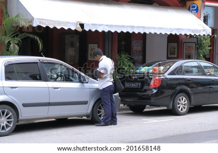 SINGAPORE - 27 May, 2014: Unidentified parking ticket inspector works in Arab Street. More than 90% of motorists pay parking fine promptly according to the URA Urban Redevelopment Authority.
