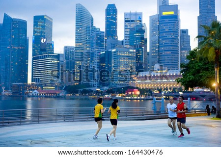 SINGAPORE - MAY 06: Unidentified people running in front of Singapore downtown on May 06, 2012 in Singapore. Singapore has been recognized as one of the best cities for runners in Asia.