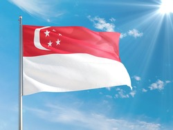 Singapore national flag waving in the wind against deep blue sky. High quality fabric. International relations concept.