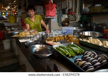 SINGAPORE - SEPTEMBER 19: A lady sells bean curd fish paste products on September 19, 2013 in a stall in Toa Payoh Market, Singapore. The traditional Asian wet market still exist in this modern city.