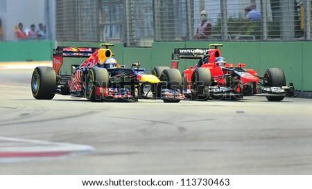 SINGAPORE - SEPTEMBER 22: Mark Webber overtaking Charles Pic at a turn during 2012 Formula 1 Singtel Singapore Grand Prix on September 22, 2012 in Singapore