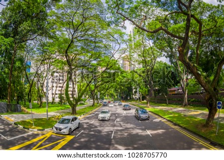 SINGAPORE, SINGAPORE - JANUARY 30. 2018: Beautiful outdoor view of many cars in a road surrounding of vegetation at public residential condominium building complex and downtown skylines at Kallang #1028705770