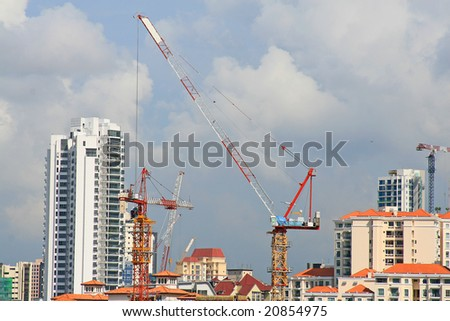 singapore skyline with construction cranes under cloudy sky. room for text.