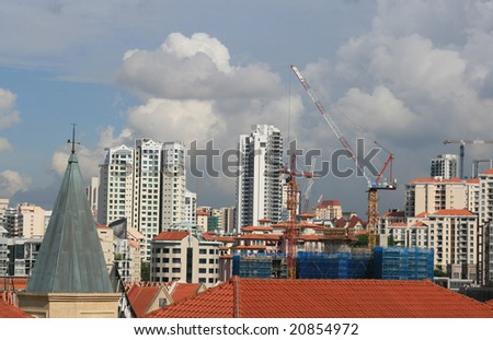 singapore skyline with construction cranes under stormy sky. room for text