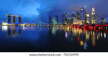 Singapore waterfront cityscape skyline with reflections in the dark blue water.