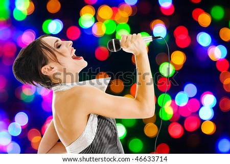 Singer artist performance at a night club against colored lights wall
