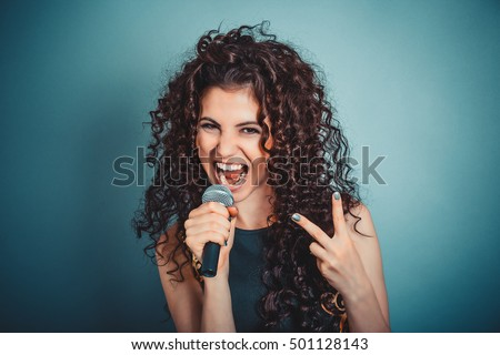 Singer. Closeup head shot sexy beautiful happy young woman lady girl singing with microphone showing peace two sign gesture blue background. Positive human emotion expression feeling life perception