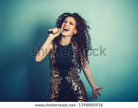 Singer. Closeup portrait head shot sexy beautiful happy young woman lady girl singing karaoke with microphone isolated blue background wall. Positive human emotion expression feeling life perception.