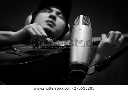 singer,guitarist,musician play guitar on condenser microphone in music recording studio / black and white processed