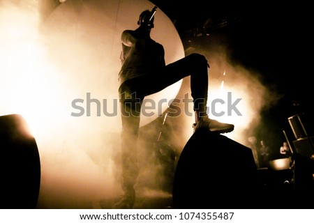 Singer on the stage. Silhouette of the singer putting his foot on a speaker. Brutal shadow of rapper on the stage. Smoke and bright stage lights in the background.