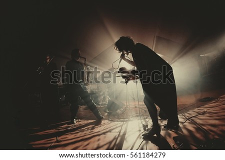 singer / vocalist performing on stage at a concert in the fog. Dark background, smoke, concert  spotlights. And saxophone player behind. #561184279