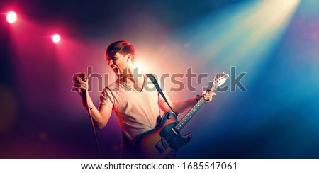 Singer with a guitar and microphone on the stage in stage lighting ストックフォト ©