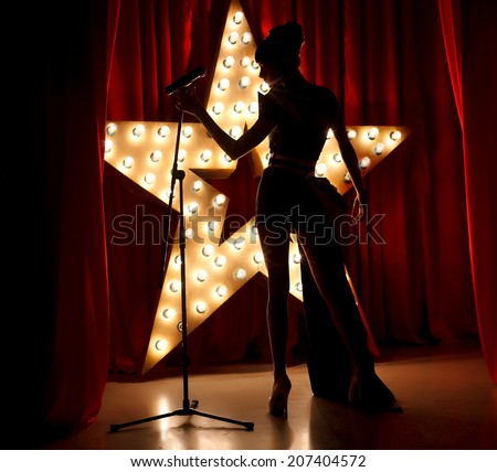 Singer woman on stage with broadway star on background