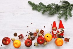 Singing gnome with apple, mandarin under christmas tree