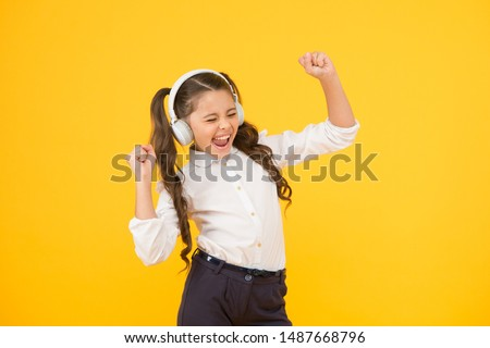 Singing in tune. Cute small child taking her singing lessons on yellow background. Adorable little girl singing her favorite song playing in earphones. The voice singing school.