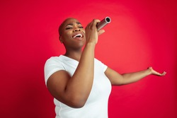Singing inspired. African-american young woman's portrait on red background. Beautiful female model. Concept of human emotions, facial expression, sales, ad, inclusion, diversity. Copyspace.