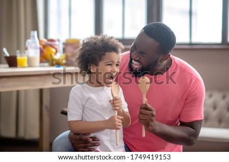 Singing songs. Cute kid with curly hair and her father holding spoons and singing a song Stockfoto ©