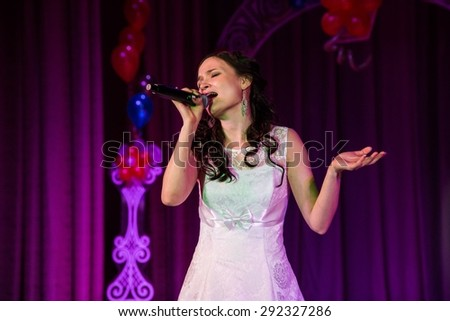 Singing woman in elegant dress with retro microphone. Beautiful glamour singer girl portrait with closed eyes against bokeh
