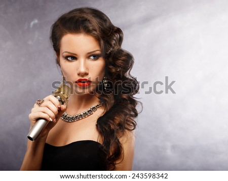 Singing Woman with Microphone. Beauty Glamour Singer Girl. Vintage Style. Song.Portrait of a glamorous girl holding a mike and singing