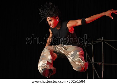 Single African male dancer dancing on the stage with black background during training session. Lit with spotlights