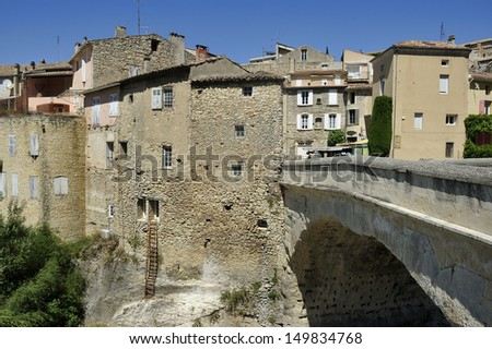 Single-arched Roman bridge over the Ouveze river in the town Vaison la Romaine , Haut Vaucluse, France