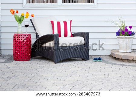 Single armchair with a red ceramic pedestal table and vase of spring tulips with a matching striped red and white cushion on a brick paved outdoor patio for a relaxing break #285407573