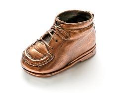 Single baby shoe on white background, bronze