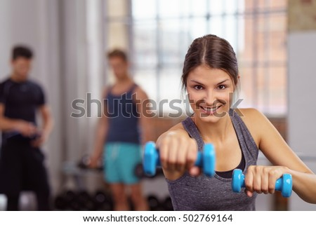 Shutterstock Single beautiful young adult woman in long dark hair with enthusiastic expression using blue dumbbell weights at gym
