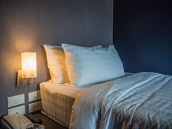 Single bed  and two pillows white cotton blanket with warm light in a cosy bed room .