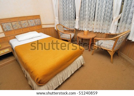 Single bed neatly done up in a high class hotel room with table and chairs. Suitable for concepts such as travel, tourism, vacation and holiday.
