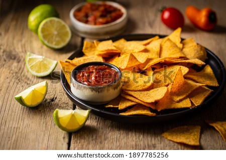 Single big black plate of yellow corn tortilla nachos chips with salsa sauce over wooden table Stock photo ©