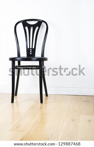 Single black modern chair on a pine floor against white wall