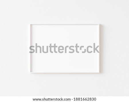 Single blank horizontally oriented rectangular picture frame with thin white border hanging on white wall. 3D illustration.