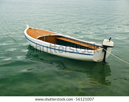 Single boat floating on a sea surface