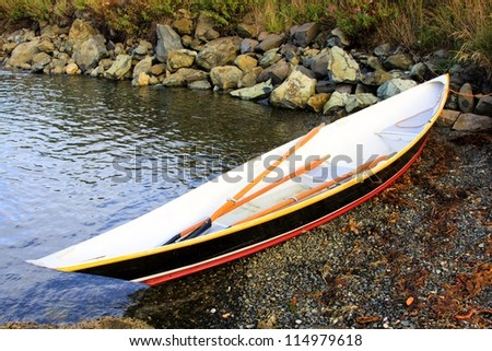 Single boat on the shore line with oars.