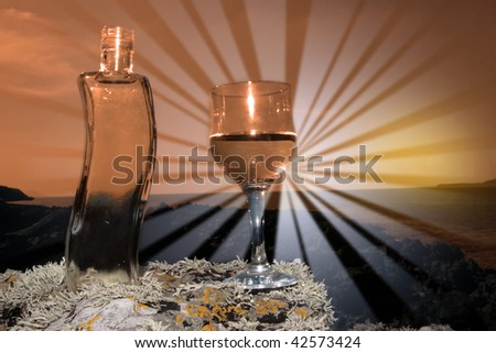 single bottle and a glass of pure natural water standing on the rocks on a beach in ireland showing a clean environment at sunset