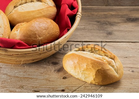 single bun and bread rolls in a basket with red napkin on a table from old wood